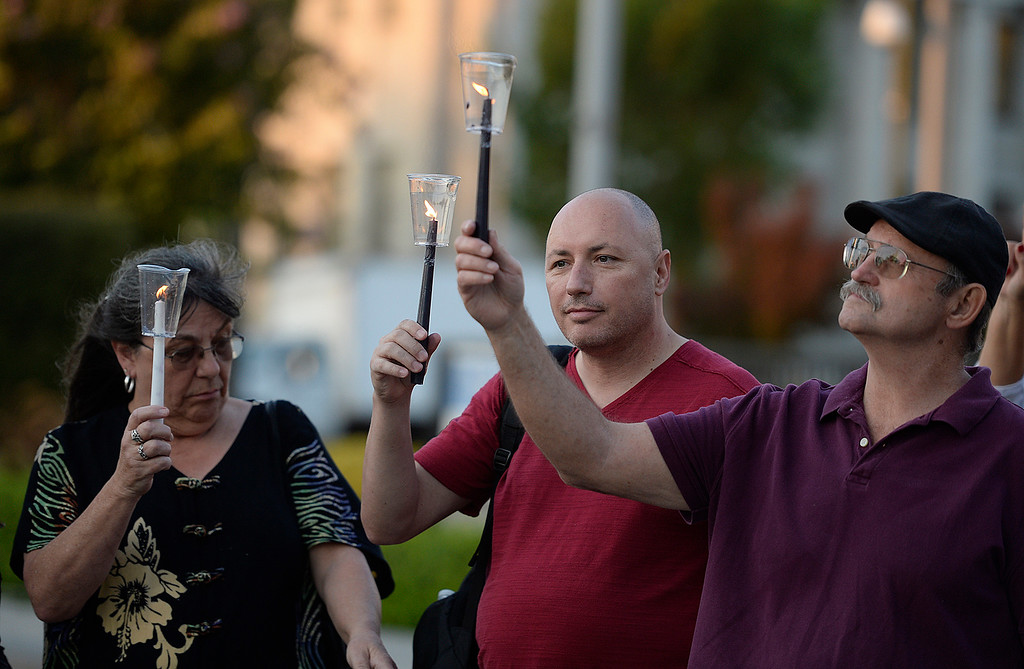 . Mary Brown (left,) Kirk Wamsley and Darrell Brown all of Benicia hold lit candles at the conclusion of a vigil held Thursday at the Solano Government Center in solidarity for people of Charlottesville, Virginia. Joel Rosenbaum -- The Reporter