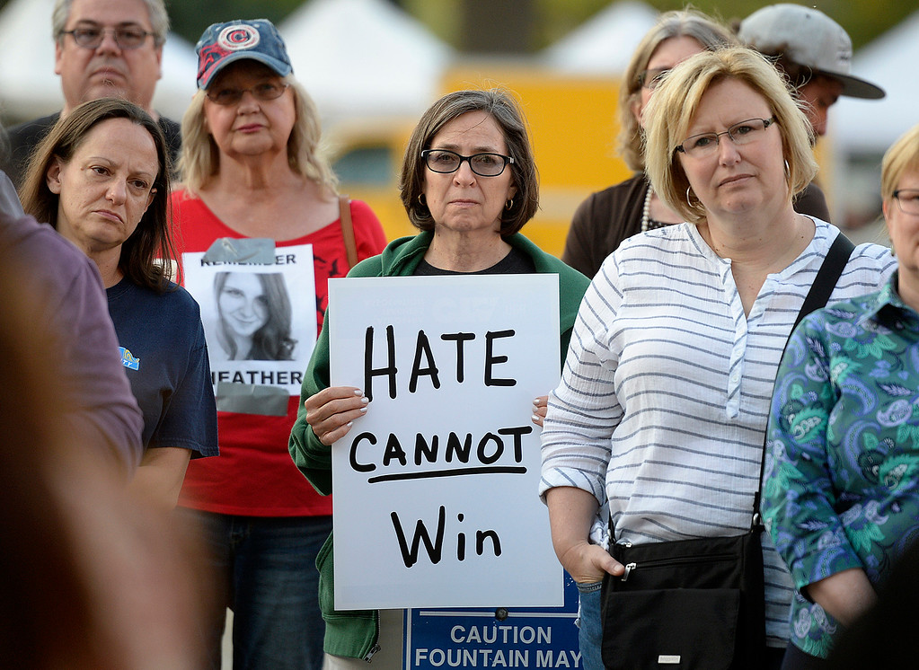 . Jeanette Wylie of Vacaville holds an anti-hate sign as she listens to Vacaville School Board President, Michale Kitzes address the crowd gathered in the plaza of the Solano County Government Center during a candlelight vigil �in solidarity with the �people of Charlottesville, Virginia. Joel Rosenbaum -- The Reporter