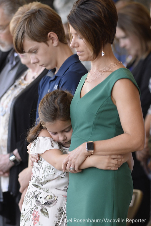 . Reagan Nelson, 9 hugs her mother, Courtney as the invocation is delivered during an Assumption of Command Ceremony for her father United States Air Force Col. Jeffrey Nelson Tuesday at Travis Air Force Base. Nelson\'s son, Tanner, 13 is at left. Joel Rosenbaum -- The Reporter