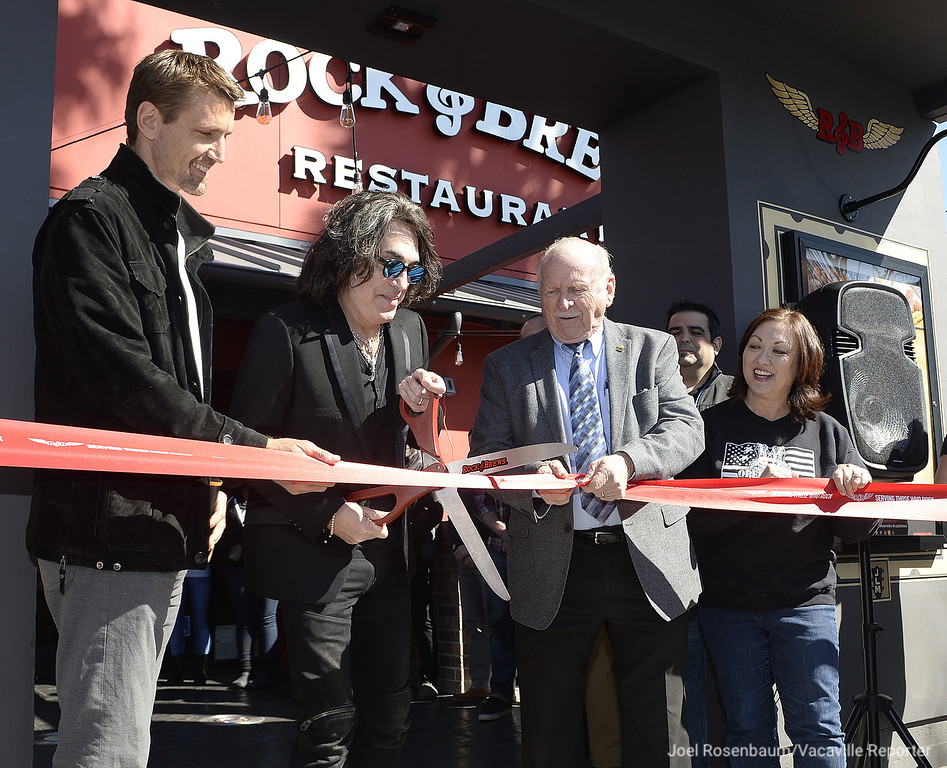 . Flanked by Rock and Brews Vacaville franchise owner, John Mesko (left) and mayor, Len Augustine,  Paul Stanley of the KISS cuts the ceremonial ribbon in front of the new restaurant in the Vacaville Commons Shopping Center. Stanley was in town Tuesday to officially open the eatery at a special event honoring both active duty and retired military.