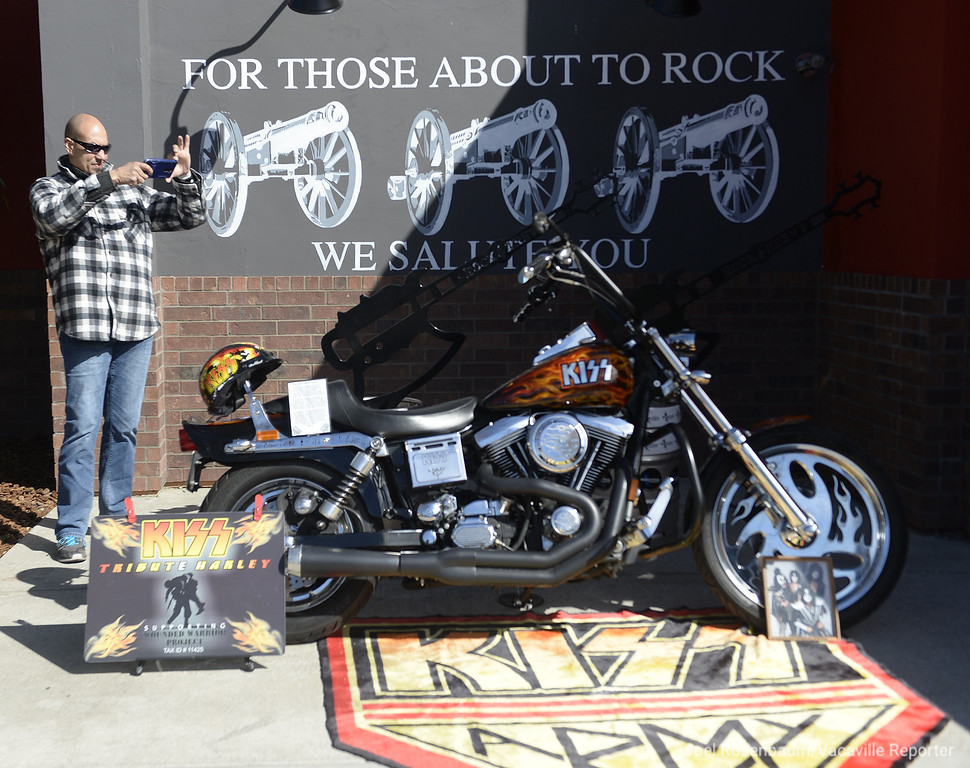 . KISS fan Ken Hetherington of Sacramento take a picture of special designed Harley Davidson motorcycle parked in front of the Rock & Brews in Vacaville that marked its grand opening Tuesday with a visit from Paul Stanley, co-founder of the band and a special luncheon that honored both active duty and retired military.