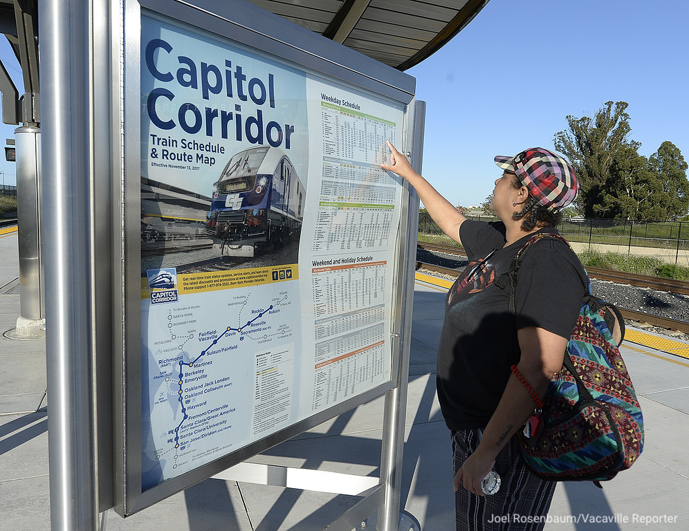 . Caprice Lipscomb of Fairfield checks the train schedule as she waits for her train ride to the Suisun train station after attending a grand opening for the new Fairfield-Vacaville Train Station Thursday in Fairfield. Lipscomb says that she rides the train frequently to visit friends in Oakland.