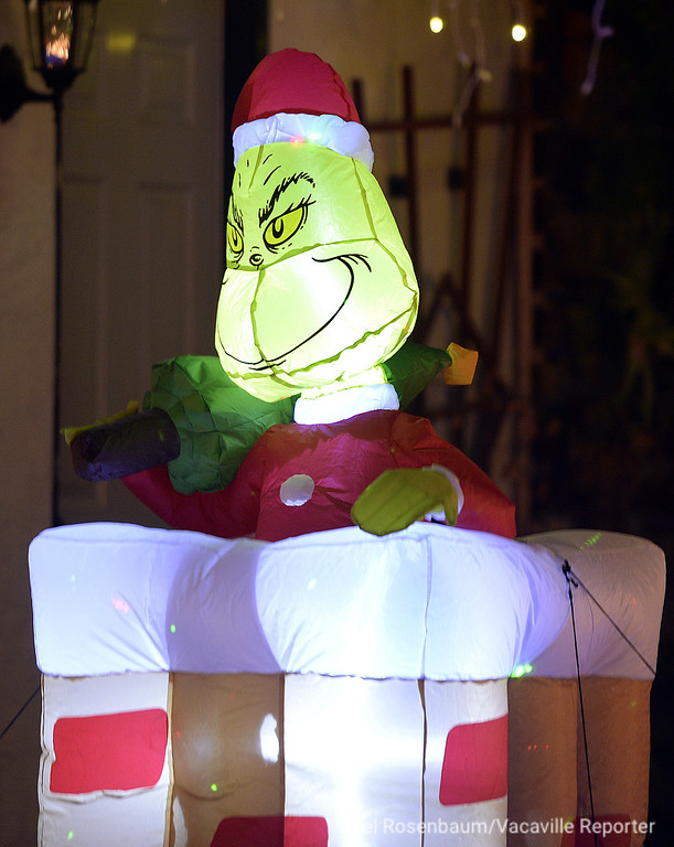 . An inflatable Grinch popping out of chimney greets visitors to the Anton family home along Cambridge Drive in Vacaville.