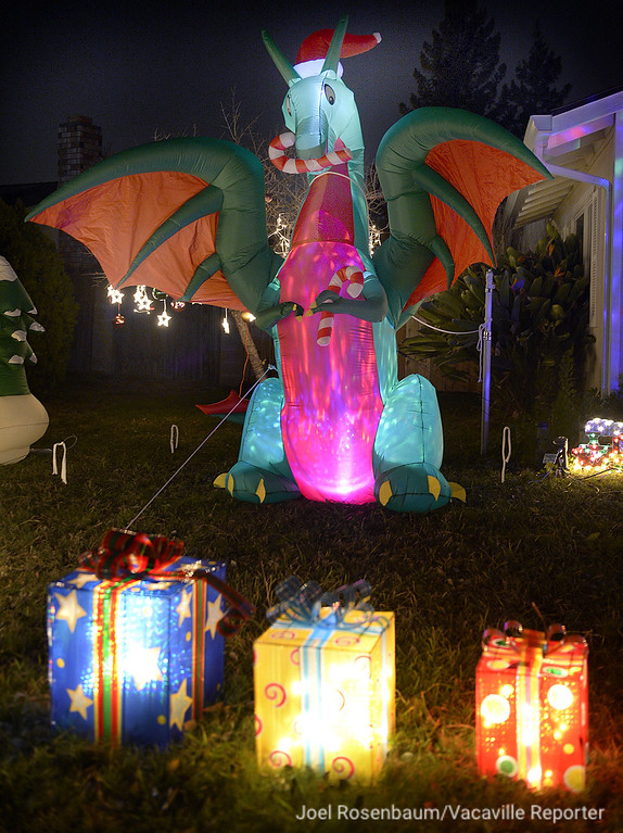 . Lighted packages are protected by an inflatable dragon wearing a Santa hat and clutching candy canes in its talons at a home in the 700 block of Northampton Drive in Vacaville.