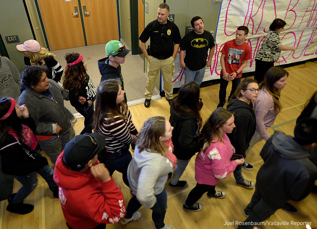 . Dixon Police Sgt. Brad Harms (middle) watches as Dixon High School students file into the gymnasium for the rescheduled Sweetheart Rally Friday at the school.