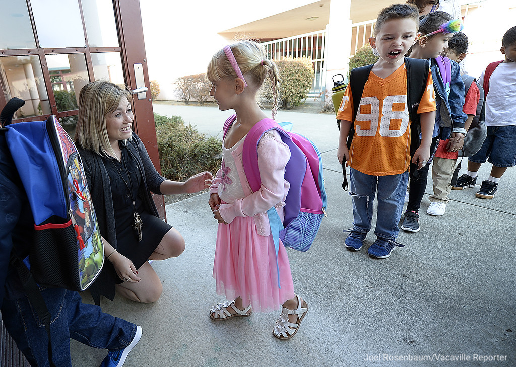 . Foxboro Elementary School kindergarten teacher, Sarah Stinnett welcomes her students into her classroom Wednesday during the first day of school for the students throughout the Travis Unified School District.