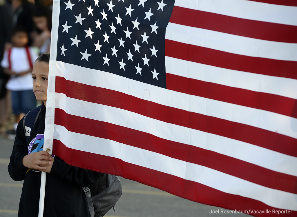 . Foxboro Elementary School third grader, Alex Castillo, 8 of Vacaville holds the American Flag as his fellow schoolmates recite the Pledge of Allegiance Wednesday during the first day of school.