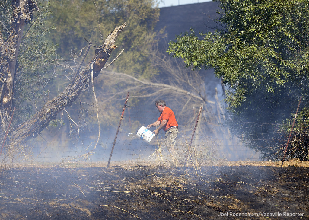 . An English Hills resident throws water from a bucket on a hot spot  from a 65-acre grass and structure fire off Skyhawk Lane. Joel Rosenbaum -- The Reporter