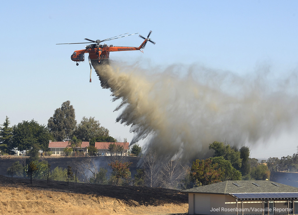 . A Sikorsky S-64 Sky Crane dumps water on a hillside along Skyhawk Lane in English HIlls as crews battle a five-alarm grass and structure fire that burned over 60 acres and two homes Saturday in rural Vacaville. Joel Rosenbaum -- The Reporter