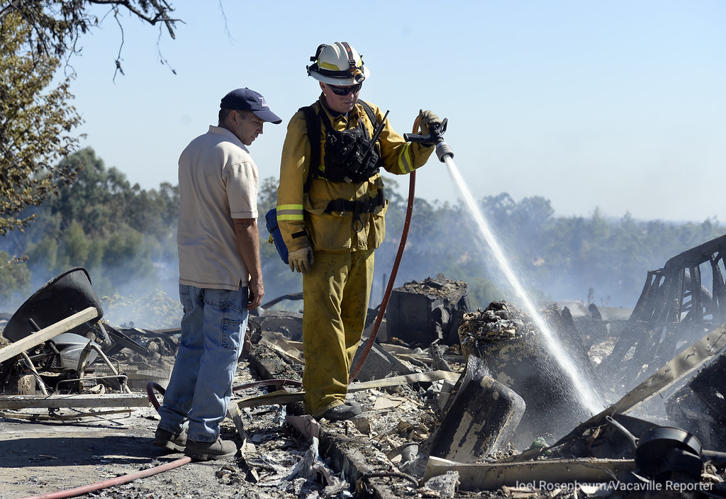 . Jeff Carmichael of Vacaville talks with a Phil Jones a firefighter with the  Vacaville Fire Protection District as he continues mop up operations on his home that was destroyed in a 65 acre five-alarm grass fire Saturday in English Hills. Crews from throughout the county battled the blaze that in addition to Carmichael\'s home destroyed a second as well as several outbuildings and vehicles. The cause is under investigation. Joel Rosenbaum -- The Reporter