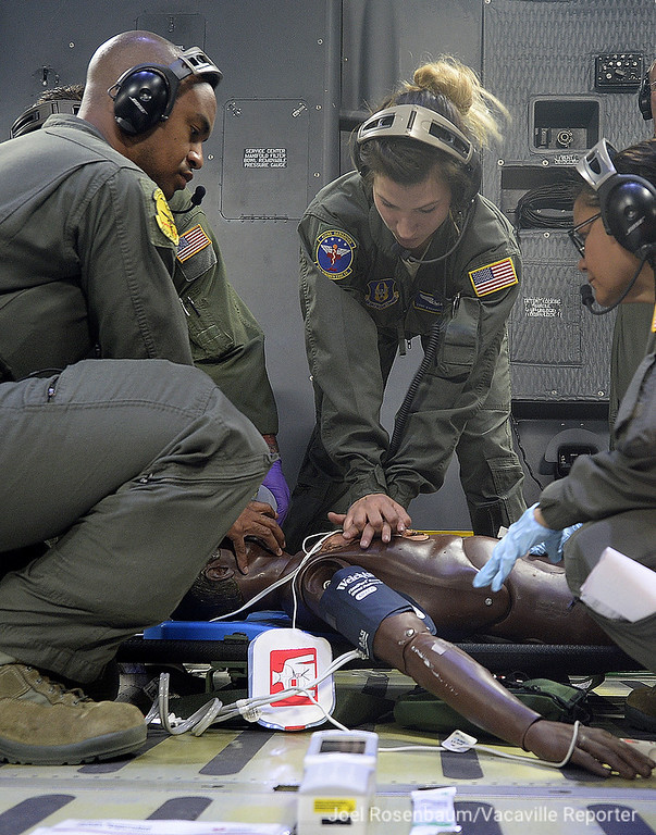 . United State Air Force aeromedical evacuation squadron members perform cardiopulmonary resuscitation on a patient while in flight in the skies above Northern California during Thursday\'s training exercise.