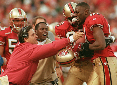 San Francisco Forty Niner wide receiver, Terrell Owens is overcome with emotions as head coach Steve Marinucci reaches to celebrate after he walks to the sidelines after his game winning catch as time expired in the NFC Wild-Card game against the Green Bay Packers in 1999.