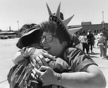 A mother wearing a novelty Lady Liberty head band hugs her son after he returned to Travis Air Force Base after his deployment to the Middle East during the first Iraq War in May of 1991.
