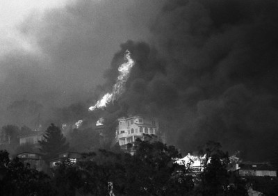 Flames and clouds of smoke erupt into the sky above Berkeley near the Claremont Hotel during the Oakland Hills Fire in October of 1991.
