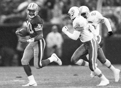 San Francisco Forty-Niner Hall of Fame wide receiver, Jerry Rice sprints away from two Miami Dolphins defensive backs in December of 1992. Rice broke the record for touchdown receptions during this game.