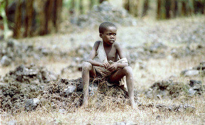 A young Rwandan boy sits on a makeshift grave near the airfield in Goma, Zaire, in July of 1994. Planes from Travis were among the first to deliver relief supplies to the area during the country's civil war