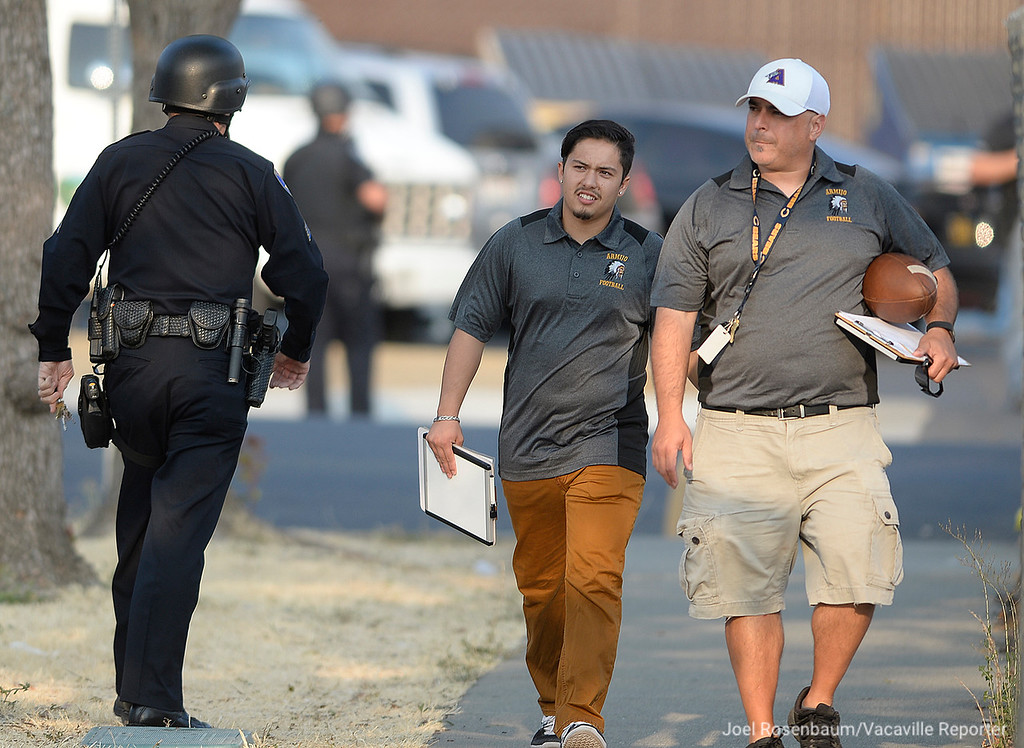 . Members of the Armijo High School football staff walk past a Vacaville Police officer to a parking lot across from the Armijo campus as they clear E. Gary Vaughn Gymnasium where they had been sent with approximately 500 students and parents who had been moved from the stadium to gym during a lockdown at the school when a homicide suspect fled from police and entered the campus.