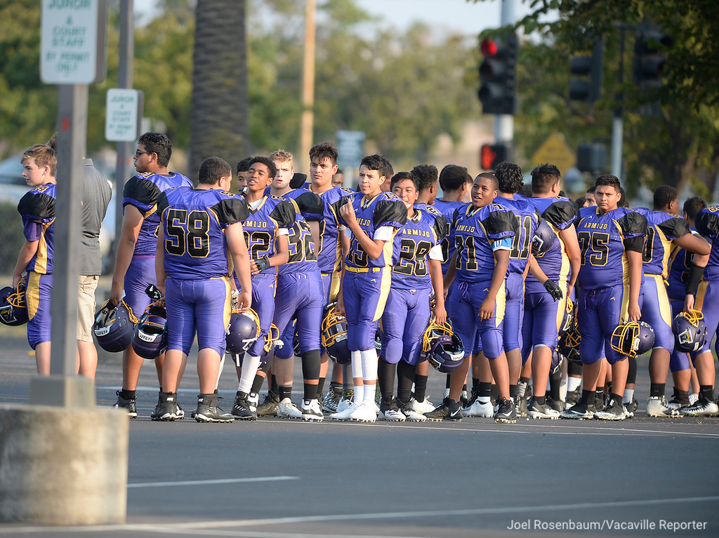 . Members of the Armijo High School junior varsity football team stand in the parking lot across from the Armijo campus as they clear E. Gary Vaughn Gymnasium where they had been sent with approximately 500 students and parents who had been moved from the stadium to gym during a lockdown at the school when a homicide suspect fled from police and entered the campus.