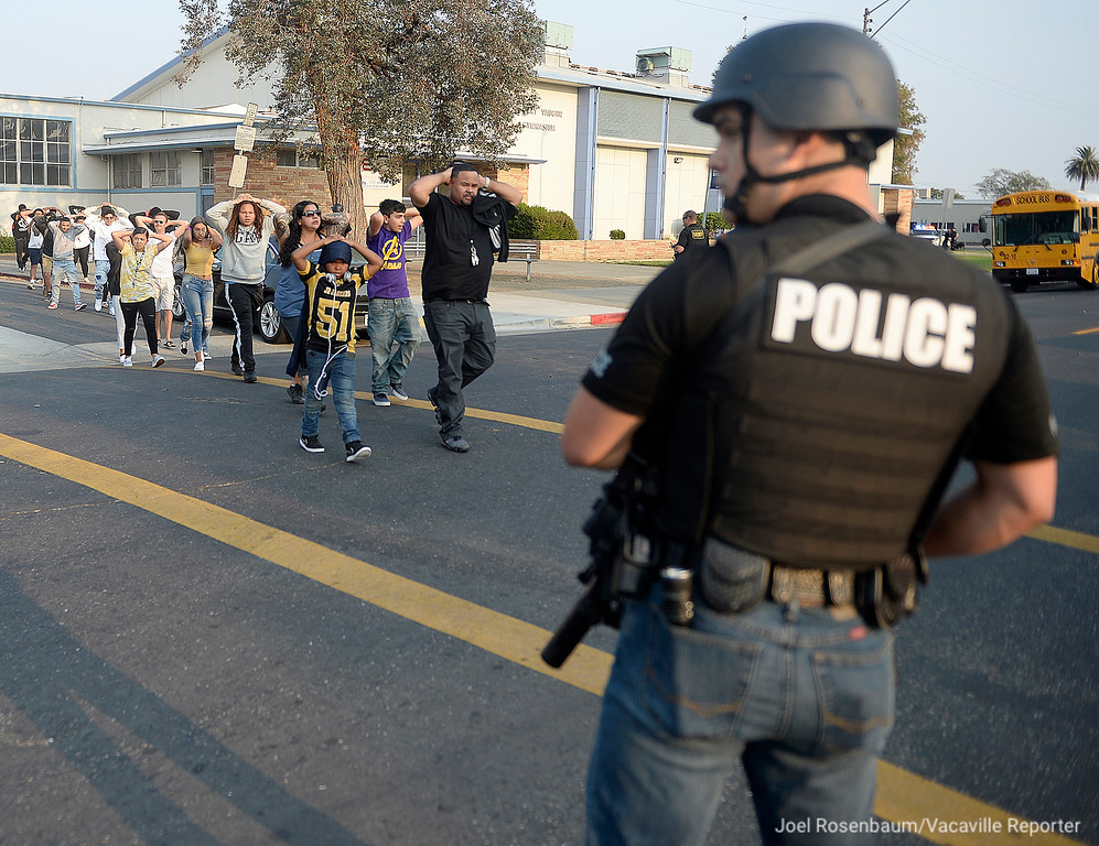 . Fairfield Police monitor students and parents as they exit E. Gary Vaughn Gymnasium at Armijo High School Friday after they lifted a lockdown at the school When a suspect from a late afternoon shooting ran onto campus and tried to hide among approximately 500 students and parents who had been moved from the stadium to gym during the lockdown. Officers were able to capture the suspect peacefully.