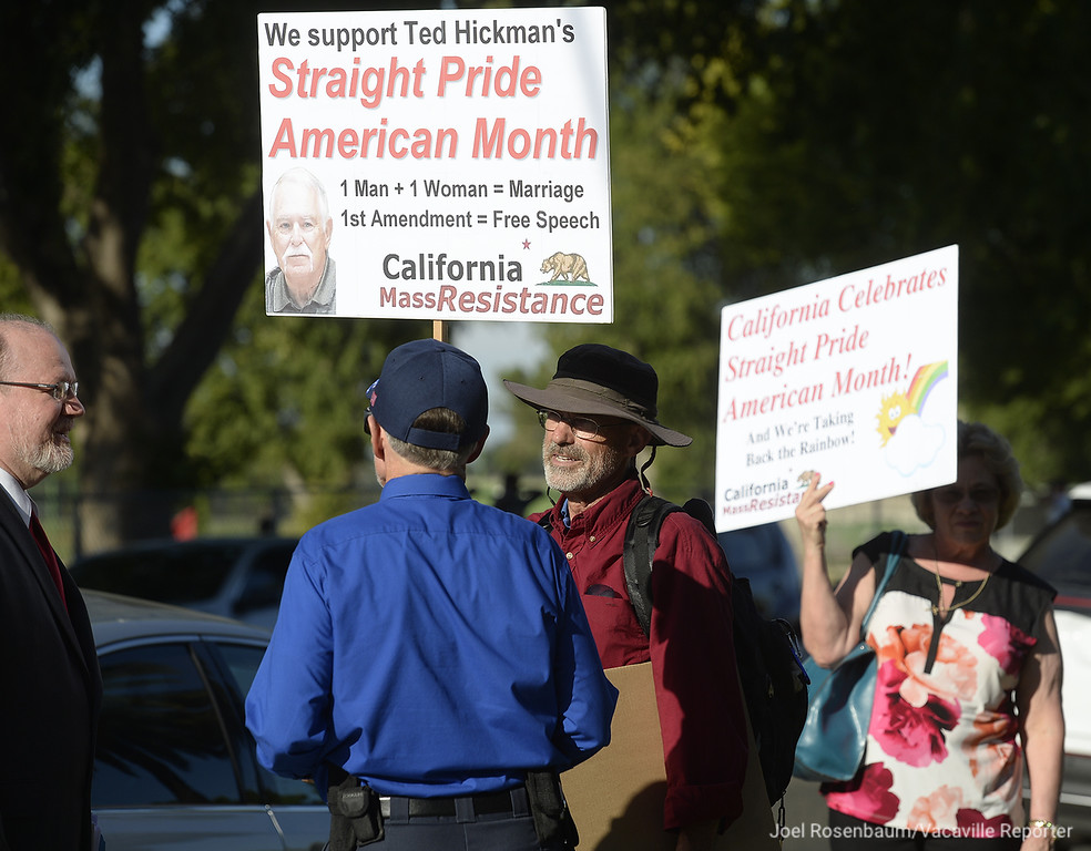 . Fred Garvey of Alameda (middle) of the group, Mass Resistance speaks with a people as he stands outside of Dixon City Hall holding a sign supporting Dixon Vice Mayor, Ted Hickman before Tuesday�s City Council meeting along with Patricia Scholl (right.)