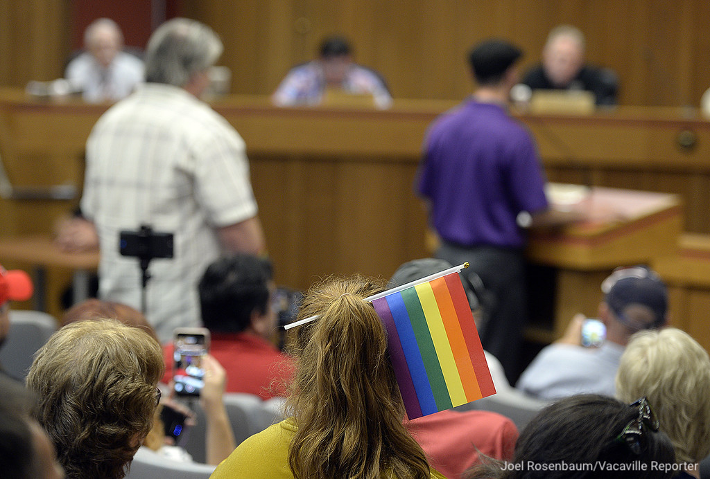 . A woman wears a rainbow flag in her hair as she sits in the Dixon City Council Chambers during Tuesday\'s meeting. Members from both sides of the issue surrounding Dixon Vice Mayor, Ted Hickman were represented inside and out of council chambers.