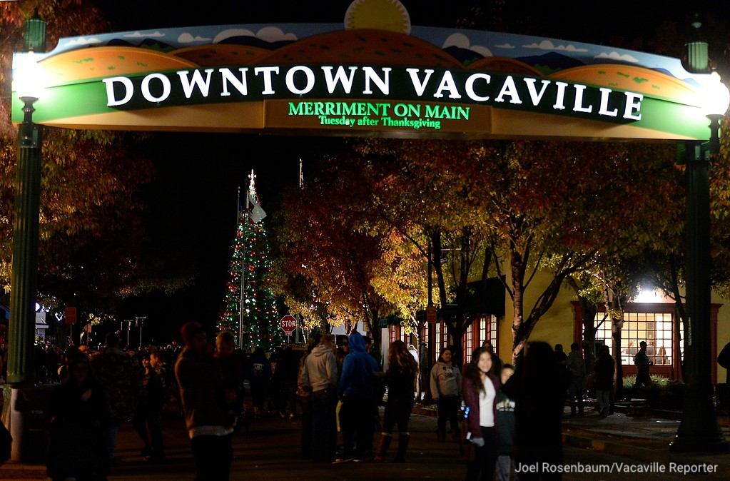 . A family stops to take a picture along Davis Street as the Vacaville Christmas Tree glows on Tuesday, after the 34th  Merriment on Main Celebration concluded.Joel Rosenbaum -- The Reporter