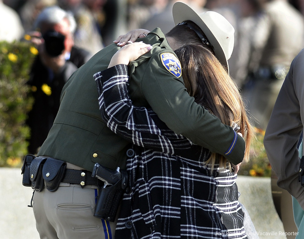 . Rosanna Camilleri (right,) widow of California Highway Patrol Officer Andrew J. Camilleri, Sr. who died in the line of duty on Christmas Eve when the patrol vehicle he was sitting in was struck by a suspected impaired driver hugs his partner, Johnathan Velasquez who was injured in the crash at the conclusion of a bell toll tribute ceremony Wednesday at the CHP Academy in West Sacramento.
