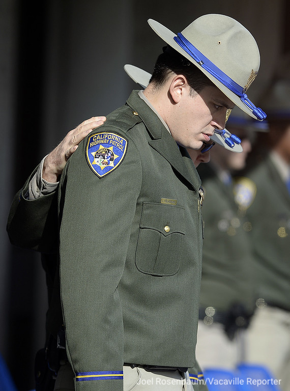 . California Highway Patrol Officer Johnathan Velasquez is escorted to his seat by CHP Capt. Tim Pearson, commander of the Hayward area office where Velasquez is stationed at the start of a bell tolling ceremony for Velasquez\'s partner officer Andrew Camilleri Sr. Velasquez and Camilleri were working Christmas Eve when their patrol vehicle was struck by a suspected drunk driver, killing Camilleri.