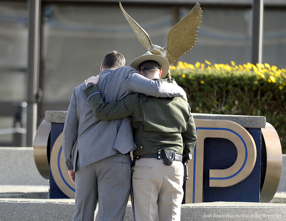 . California Highway Patrol Officer comfort each other while standing in front of the memorial fountain at the CHP Academy in West Sacramento Wednesday before a bell toll ceremony for officer Andrew Camilleri Sr.