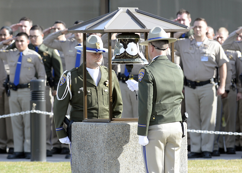 . California Highway Patrol Officers and Honor Guard members Mike Paulson (left) stands at attention as Rob Cullinan rings a bell in memory of CHP Officer, Andrew J. Camilleri, Sr. who was killed in the line of duty on Christmas Eve when the patrol vehicle was sitting in was struck by a suspected impaired drive while it was parked on an on-ramp to Interstate 880 in Hayward.