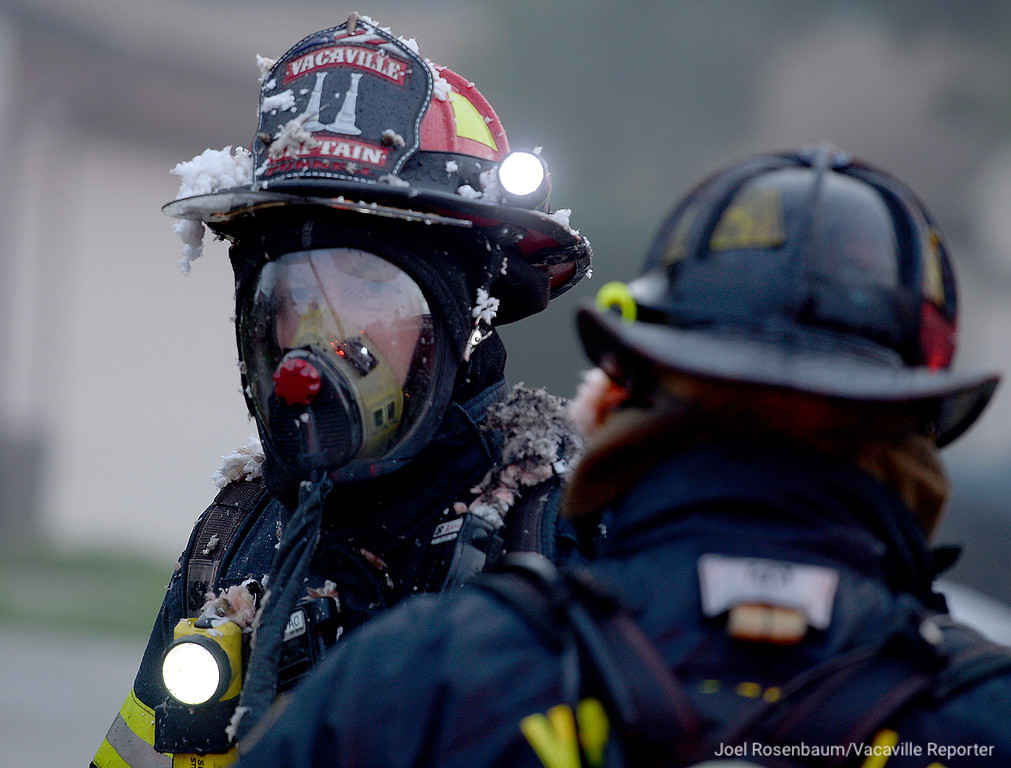 . Vacaville Fire Department Captain, Ryan Purnell waits to get an oxygen bottle changed on his breathing apparatus before re-enering a home at 218 Plantation Way as he continue the attack of a two-alarm structure fire at the home Friday afternoon.