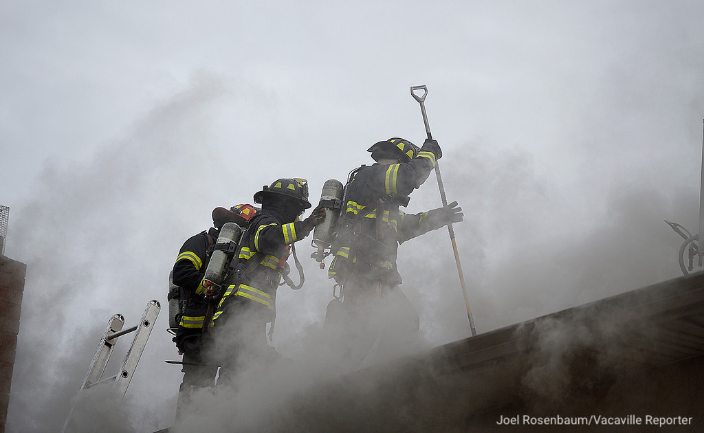 . Vacaville firefighters (from left) Captain Greg Chaloner, engineer Mindy Simpson and firefighter/paramedic, Michael Donnelly cut a ventilation hole on the roof of a house in the 200 block of Plantation Way.