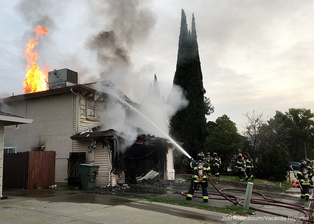 . Flames erupt into air from a ventilation hole as Vacaville Fire Department firefighters continue their battle of a two-alarm structure fire at a home on 218 Plantation Way Friday afternoon.