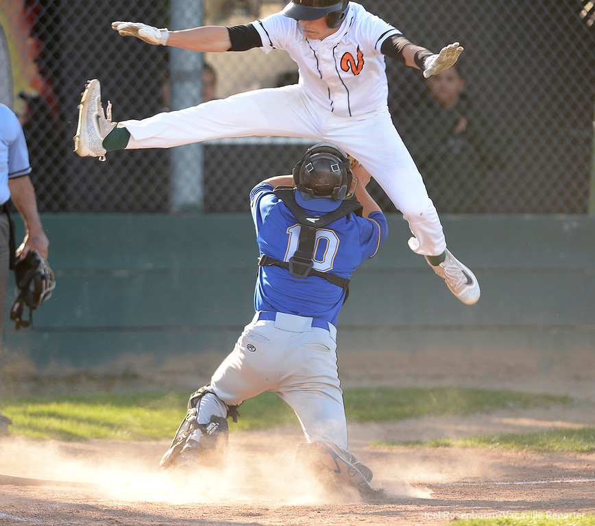 . Vacaville High\'s Tyler Bosetti hurdles Benicia High School catcher, Alejandro Soto during the Bulldogs 10-run third inning rally in their 11-6 victory over the Panthers Friday at Vaca High.
