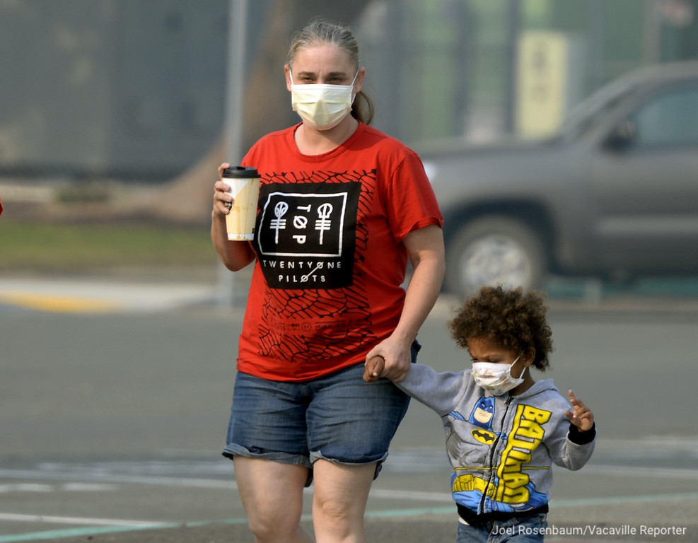 . Wearing protective masks, Amanda Johnson and her son, Elisha, 3 of Fairfield walk to the evacuation center at Solano Community College Tuesday morning. The center opened after a mandatory evacuation order was issued by the Solano County Sheriff late Monday and is being run by student volunteers from the college as well as personnel from the Salvation Army affording displaced residents shelter while fire operations continue.