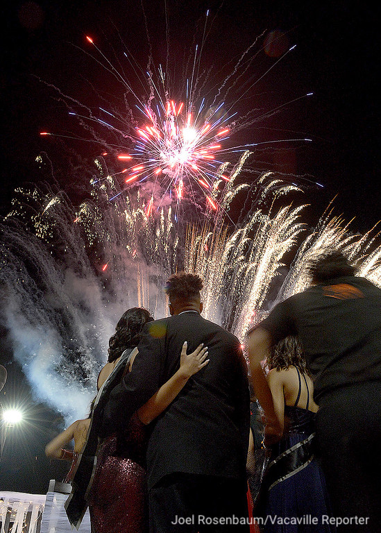 . Members of the Vacaville High School Homecoming Court gaze skyward fireworks explode overhead at the conclusion of coronation ceremonies at halftime of the Bulldogs non-league game against Granite Bay High School Friday at Tom Zunino Stadium.