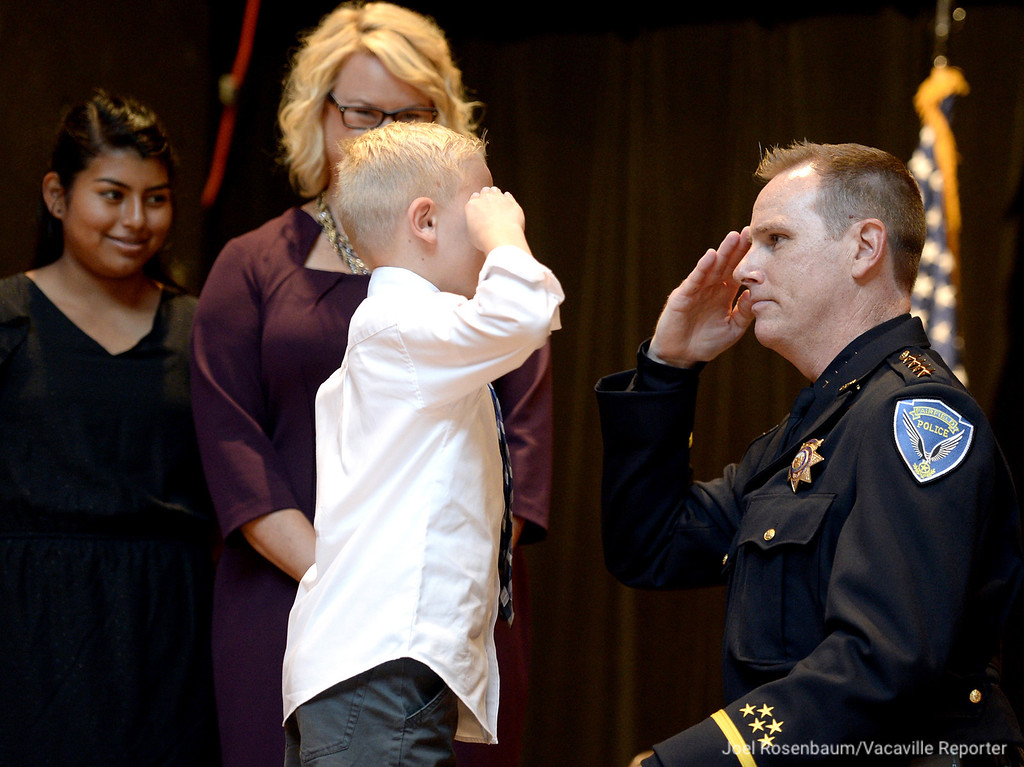 . Jackson Fenn, 10 salutes his father, Randy after he pinned his police chief\'s badge to his uniform as his sister, Lilliana, 12 (left) and his mom, Stacie smile with pride during swearing in ceremony Monday at Willow Hall at the Fairfield Community Center.