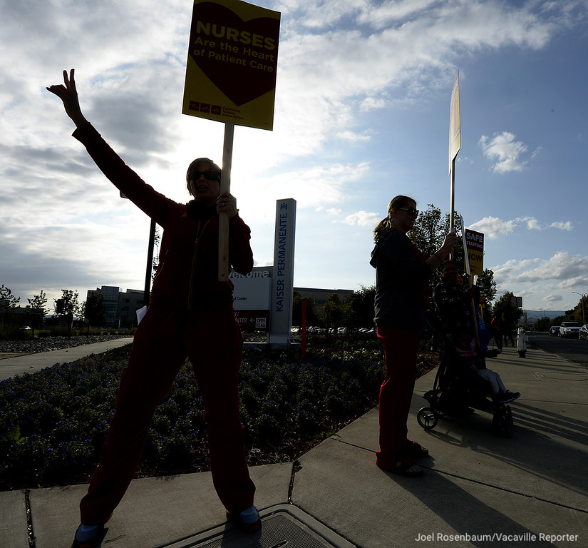 . Alejandra Bello (left) a registered nurses in the medical/surgery unit at Kaiser Medical Center, Vacaville acknowledges the honking of a motorists driving along Vaca Valley Parkway as she participates in an information picket Thursday in front of the Vacaville campus.
