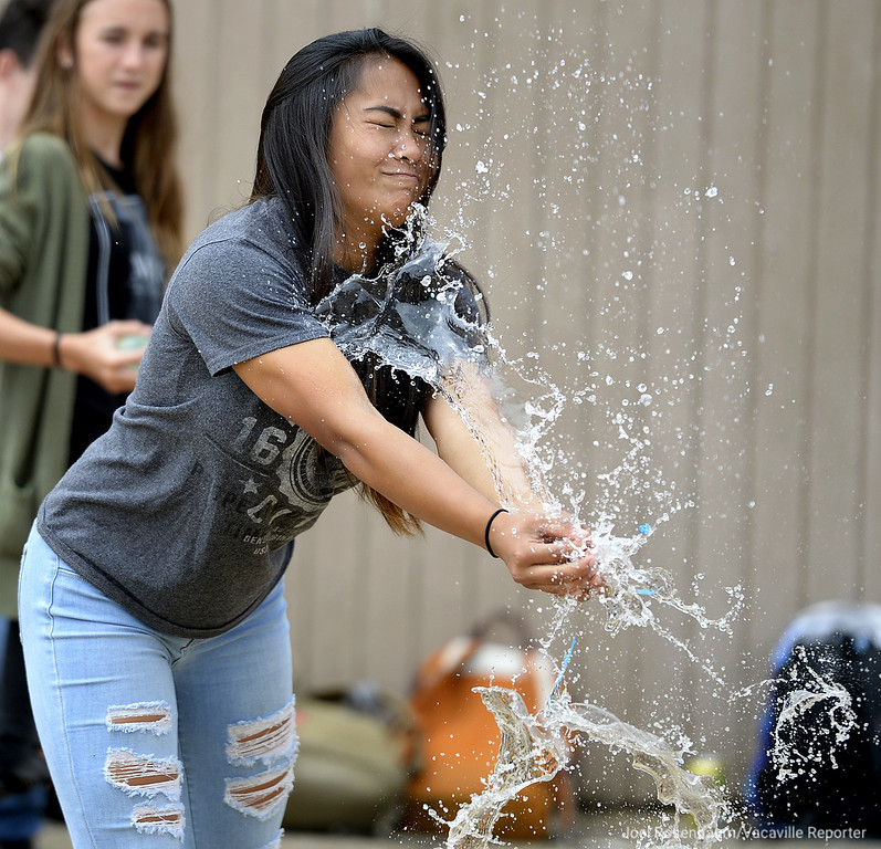 . Maila Bautista, 14 a freshman at Vacaville High School reacts as a water balloon bursts in her hands as she makes a failed attempt to catch it while participating in a balloon toss during lunchtime Thursday to mark homecoming week at the school. Members of the Student Council organized a week-long celebration during lunch all leading to Friday night\'s football game aginst Granite Bay High School.