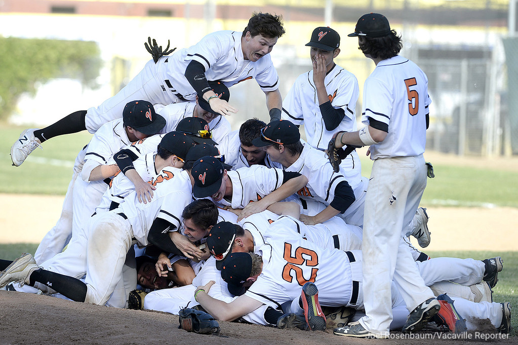. Members of the Vacaville High baseball team dog pile on the pitcher\'s mound after their 5-1 victory over their rival, Will C. Wood Wednesday at Vaca High. With the victory, the Bulldogs clinched the MEL title Joel Rosenbaum -- The Reporter