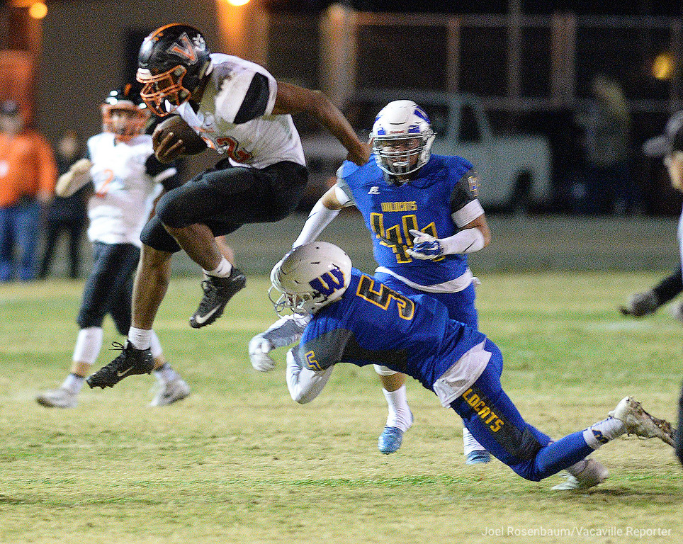 . Vacaville High School running back, Timothy Jackson leaps over Will C. Wood\'s Isaac Pewitt during a big first quarter run in the Bulldogs\' 49-7 rout of their rivals during the 2017 Black and Blue Bowl Friday at Tom Zunino Stadium.