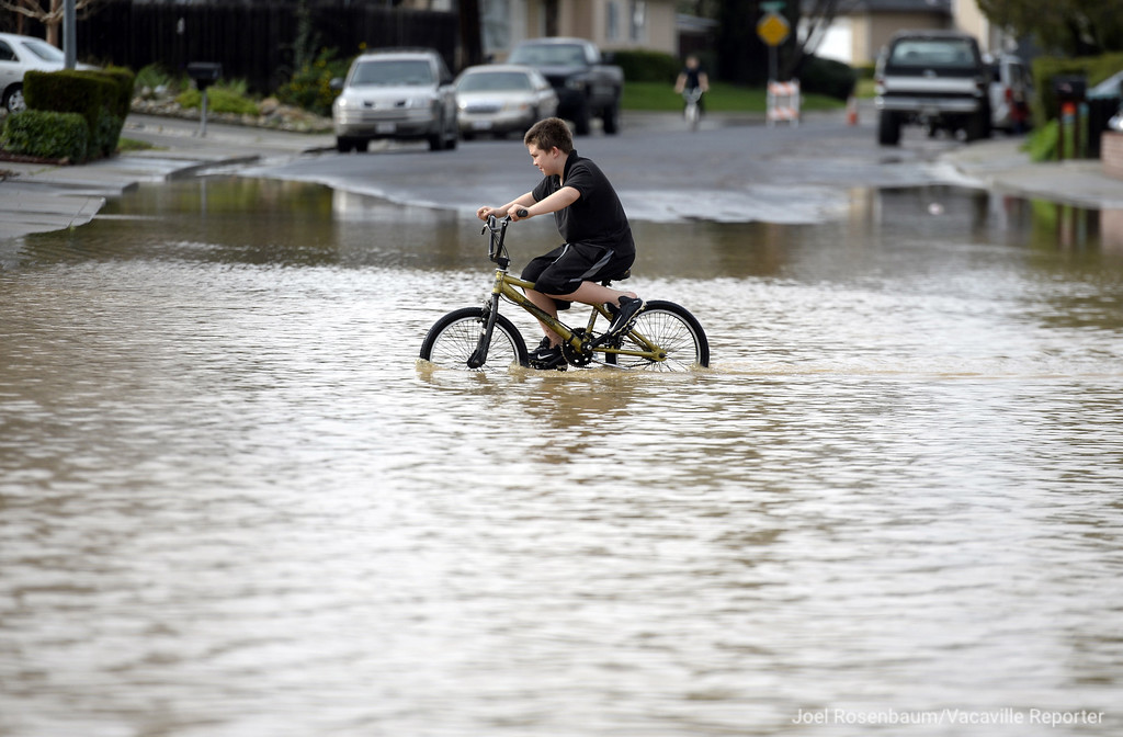. Gavyn James, 10 of Vacaville, California rides his bike across Brookdale Drive which flooded during the rain storm Tuesday, February 7, 2017. According to the rain gauge at the Ulatis Community Center the city has received about an inch and quarter of rain within the last 24 hours.