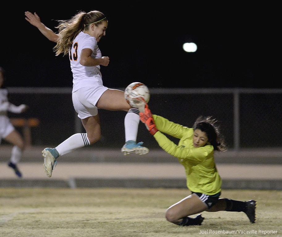 . Vacaville High\'s Jenna Bosetti has her shot blocked by Dixon High goalie, Belle Del Leon late in the first half of the Bulldogs 2-0 victory over the Rams Thursday at Tom Zunino Stadium.  Bosetti scored one of the two goal for the \'Dogs.