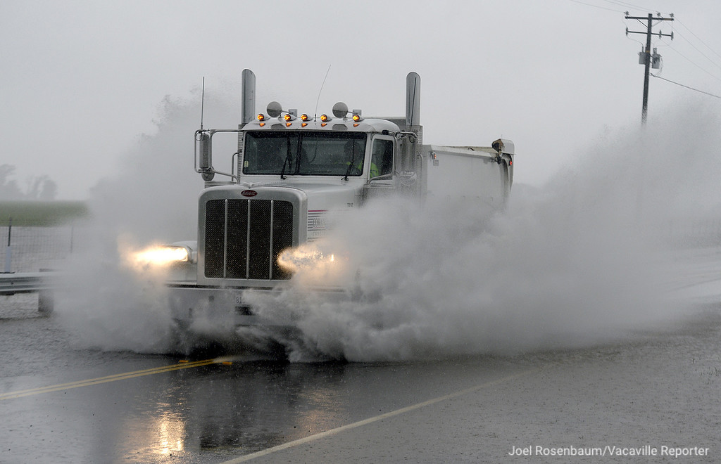 . A commercial dump truck plows through the flooded roadway along Highway 113 near Hay Rd in rural Solano County. With Tuesday\'s heavy rainfall several roads around the county were closed due to flooding.