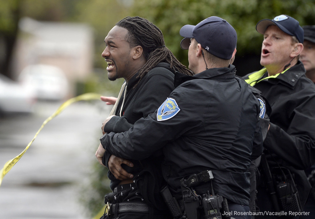 . A grief-stricken man who may have know the victim is escorted by Fairfield Police Officers from the crime scene after ran through the police tape in an attempt to see the individual who was found shot inside a vehicle parked on Great Jones Street.