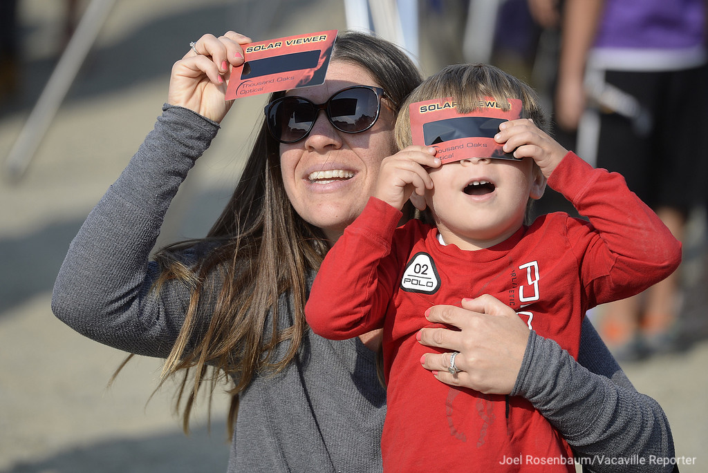 . Using special eclipse viewers, Dominque Marchak  and her young son, Cal take a look at the total eclipse as it comes into view through the light clouds in the skies above Rush Ranch Monday in Suisun.
