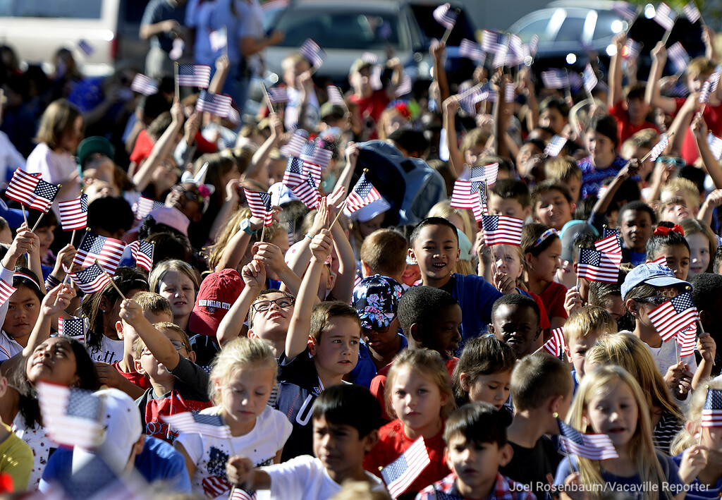 . Students from Travis and Scandia Elementary School wave American Flags at the conclusion of 12th annual Remembrance Walk Tuesday at the Airman and Family Readiness Center at Travis Air Force Base.