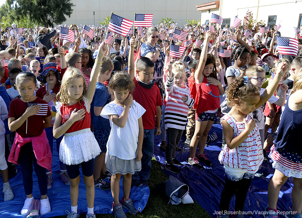 ". Elementary School students from both Scanda and Travis Elementary School on Travis Air Force Base wave American Flags as they stand while ""Taps\"" is played over the base\'s public address system at 9:37 a.m. to mark when the time when American Airlines Flight 77 crashed into the Pentagon on 9/11."