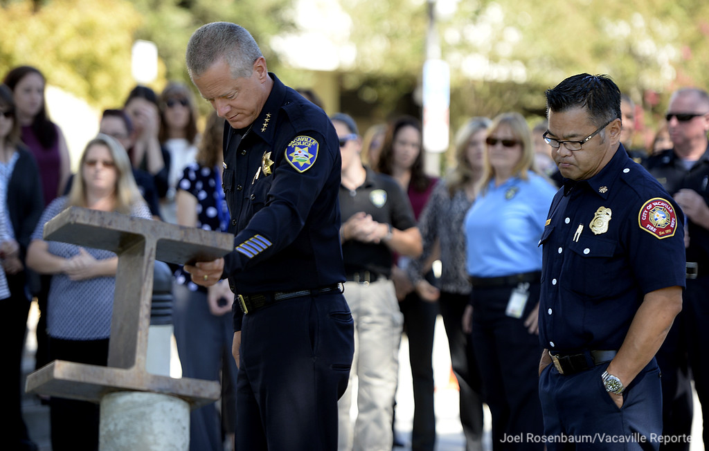 . Vacaville Police Chief, John Carli places his hand upon the 9/11 Memorial after he and fire chief, Kris Concepcion (right) lead a small ceremony Tuesday in front of the police department. The memorial, an I-beam from the World Trade Center was dedicated in 2006.