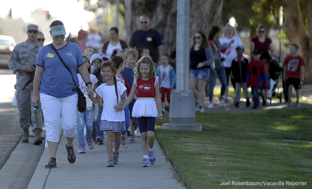 . Studnets, teachers and volunteers from Scandia Elementary School walk along Travis Avenue on Travis Air Force Base toward the Airman and Family Readiness Center Tuesday during the 12th annual Remembrance Walk.